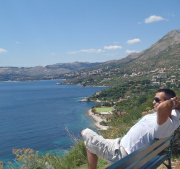 Man is seen sitting down and relaxing overlooking beautiful Dubrovnik area panorama on a Dubrovnik day tour