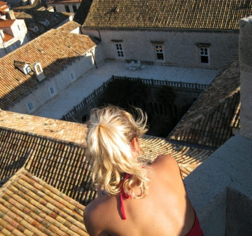 Woman is seen overlooking red city roof tops on a Dubrovnik tour