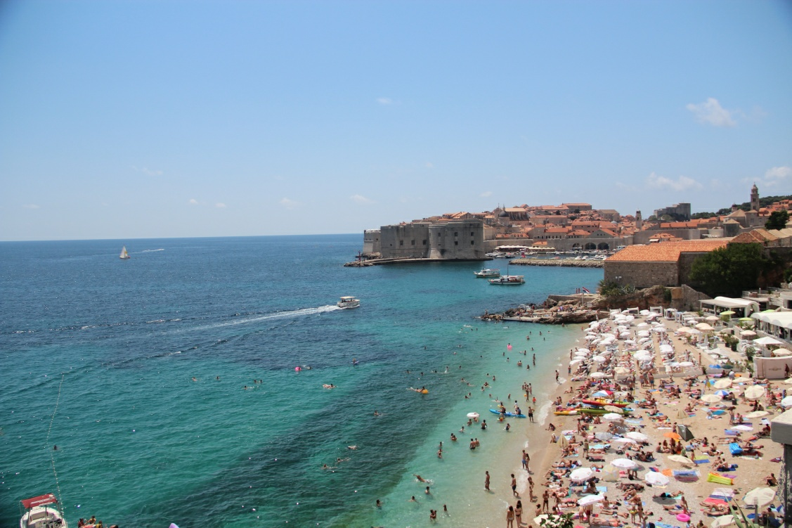 Dubrovnik panorama photo features crowds of people swimming on Banje beach just in front of Dubrovnik