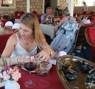Woman is seen enjoying sea food and drinking wine in a Dubrovnik restaurant