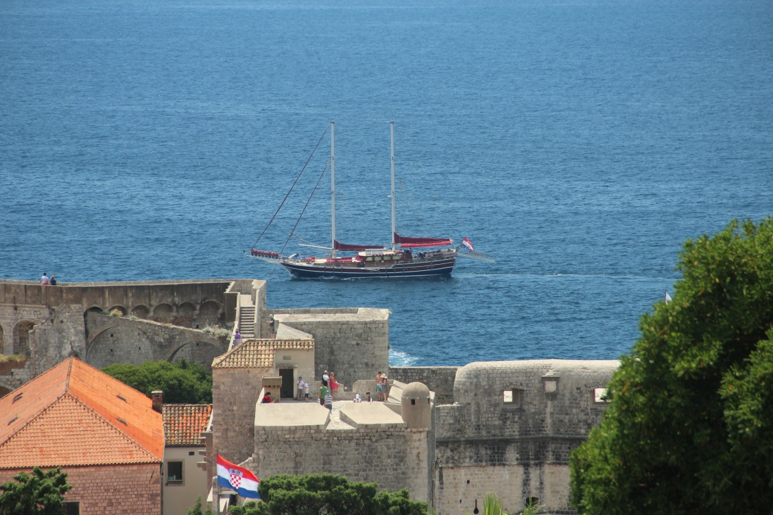 A tour boat can be seen sailing in front of Dubrovnik walls